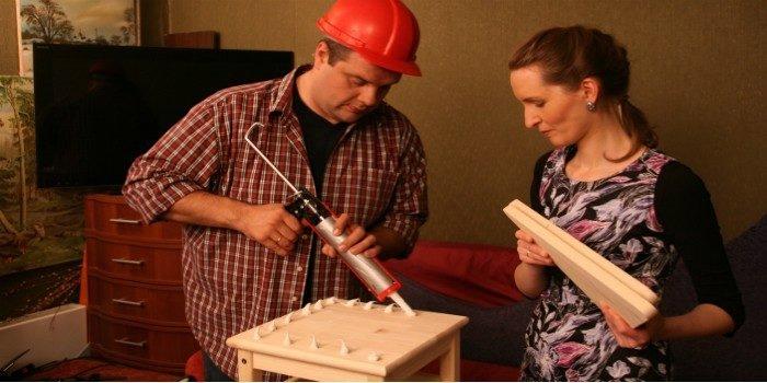 Мужчина и женщина используют жидкие гвозди для склейки дерева