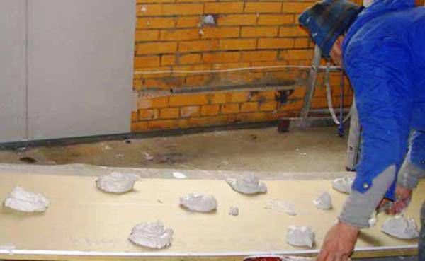 Гипсокартон иногда крепят на несколько лепёшек, при этом всё пространство между стеной и листом не заполняется клеем