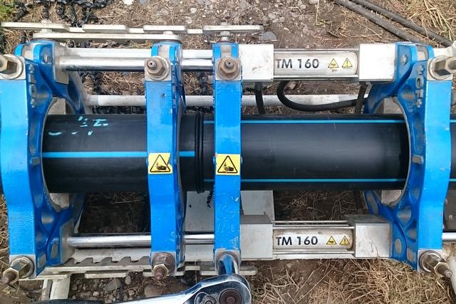 Сварка водопроводных труб ПНД встык в специальном аппарате. Стадия сжатия прогретых концов с образованием сварочного шва.